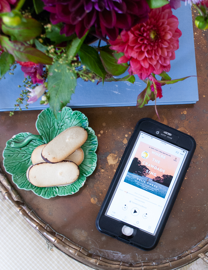 Where the Crawdads Sing by Delia Owens audio book displayed on phone sitting on brass tray with dahlia floral arrangement and cookies
