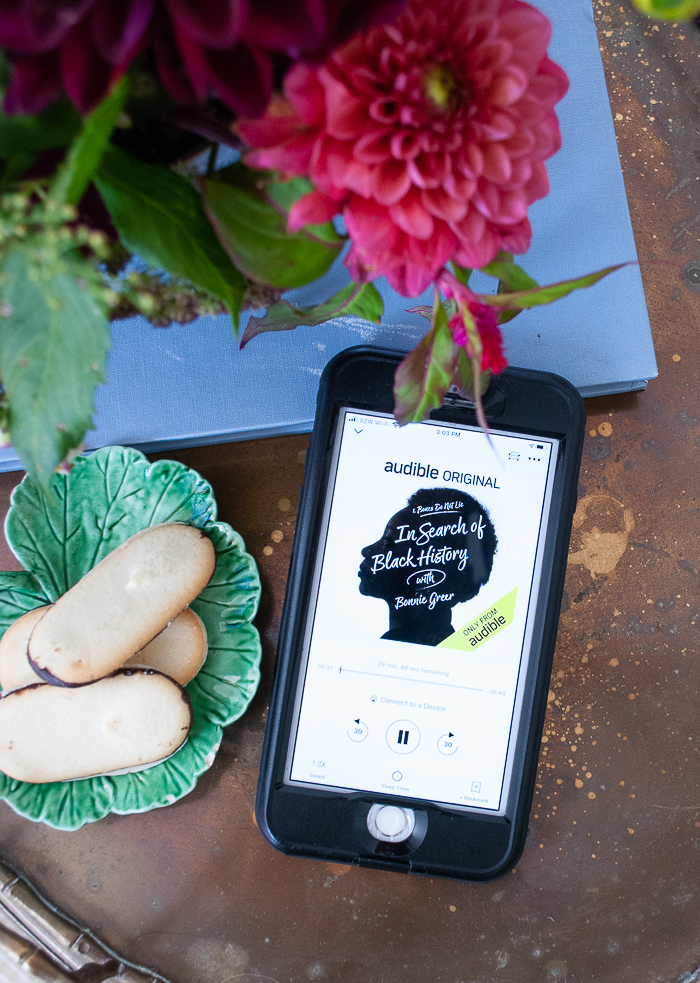 In Search of Black History with Bonnie Greer audio book displayed on phone sitting on brass tray with dahlia floral arrangement and cookies