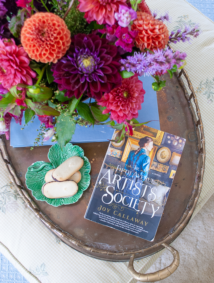 The Fifth Avenue Artists Society by Joy Callaway on brass tray with fall floral arrangement and cookies