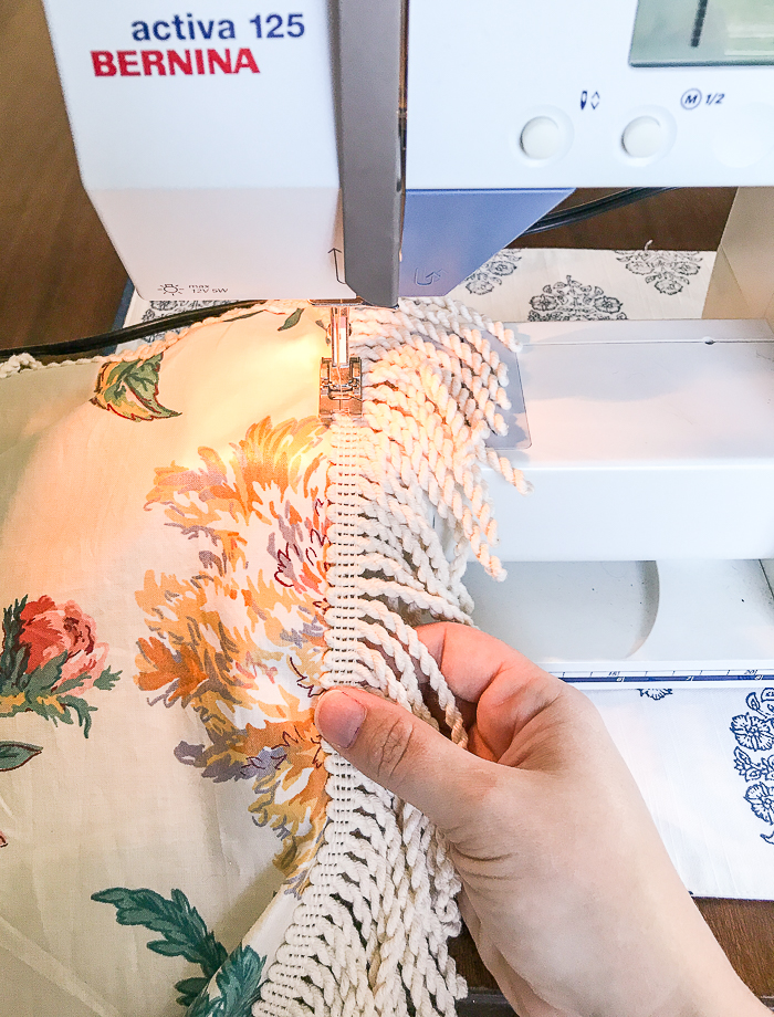 Katherine sews fabric and fringe together using a sewing machine