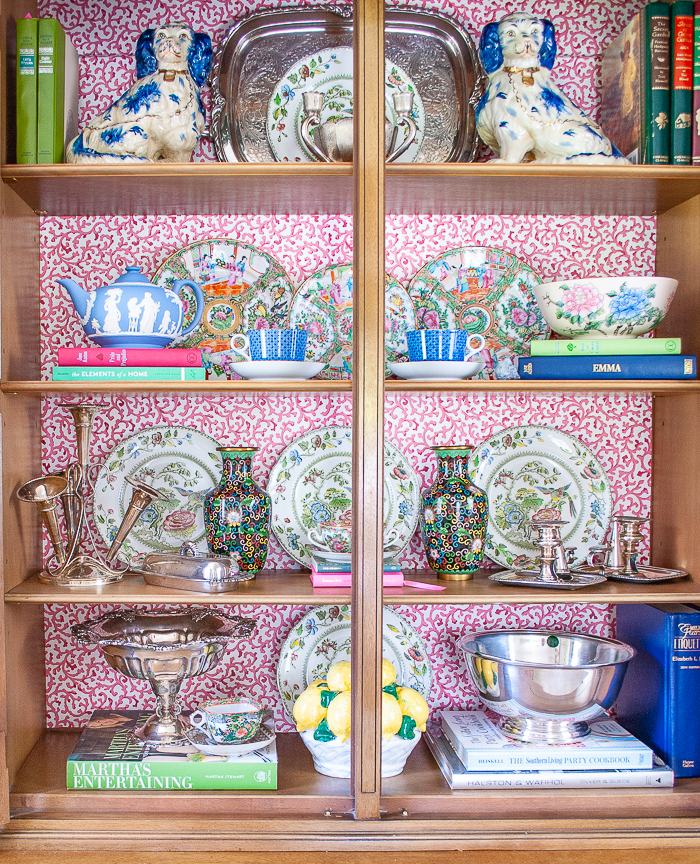 Styling a china cabinet tips using Staffordshire spaniels, books, rose medallion plates, and silver