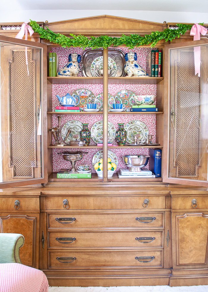 Full view of china cabinet with doors open and shelves styled