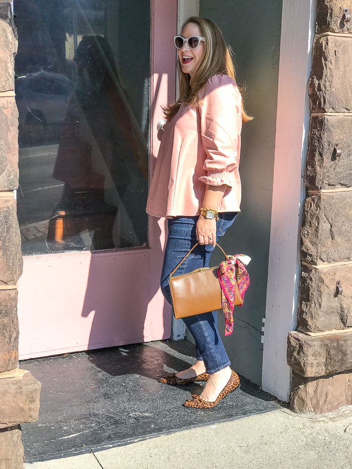 Katherine posing with pink door that matches her pink Easton blouse from Tuckernuck