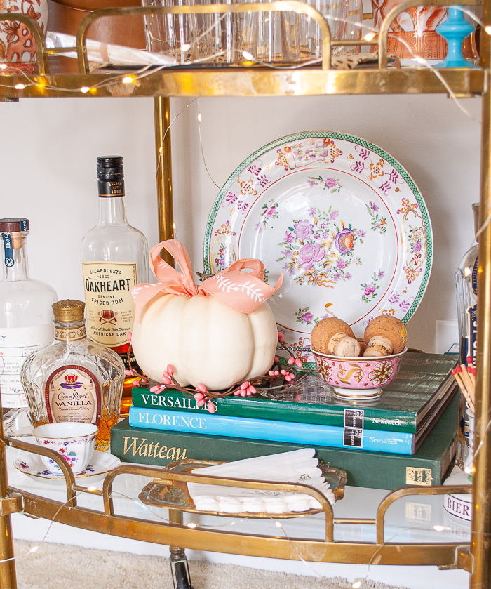On bottom of bar cart white pumpkin with pink bow and antique floral plate