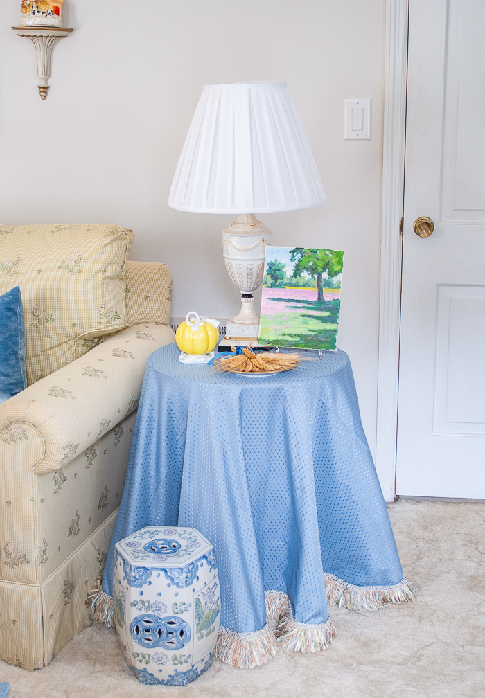 Skirted side table with blue fabric, yellow mottahedeh pumpkin, and landscape painting