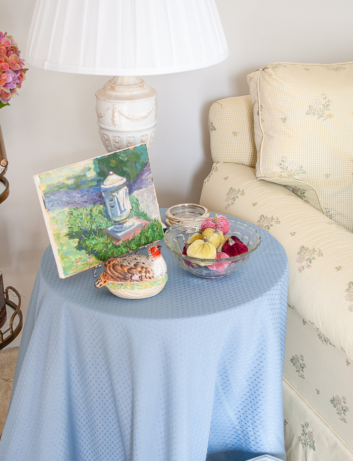 Side table draped in blue linen with small painting on easel, urn style lamp, Mottahedeh quail box, and bowl of pumpkins.