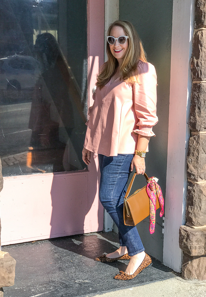 Katherine posing with pink door that matches her pink faux leather Easton blouse from Tuckernuck