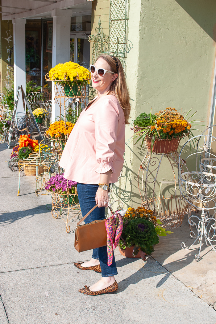 Katherine in pink Easton faux leather top, dark wash jeans, and leopard print flats - Natalie from Sarah Flint standing on sidewalk