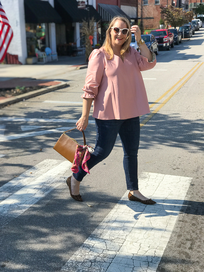 Katherine crossing street in downton Clinton wearing leopard print flats and pink top for fall look