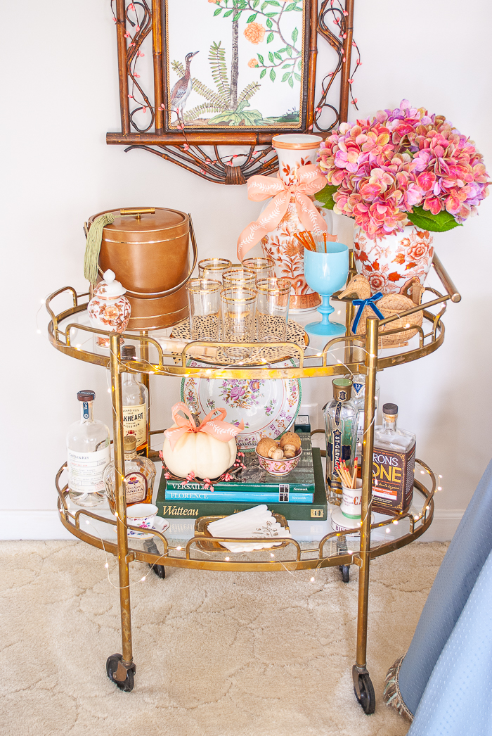 Vintage brass bar cart stocked with liquor, vintage glassware, and decorated for fall with hydrangea and a white pumpkin