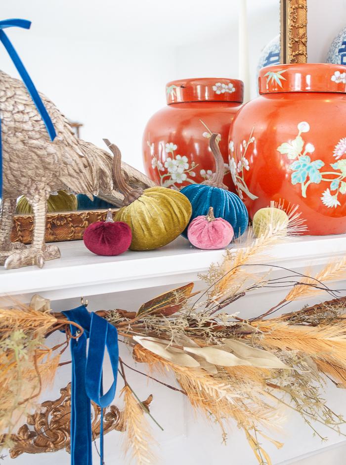 Detail of velvet pumpkins in jewel tones on fall mantel