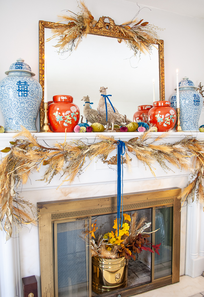 A formal living room with a fall mantel featuring velvet pumpkins, blue and white temple jars, coral red ginger jars, and autumn garland