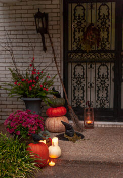 Candle light glows at this front door at dusk. Decorate for Halloween this year with a witchy front door by adding a witches hat, broom, and lantern to your autumn decor