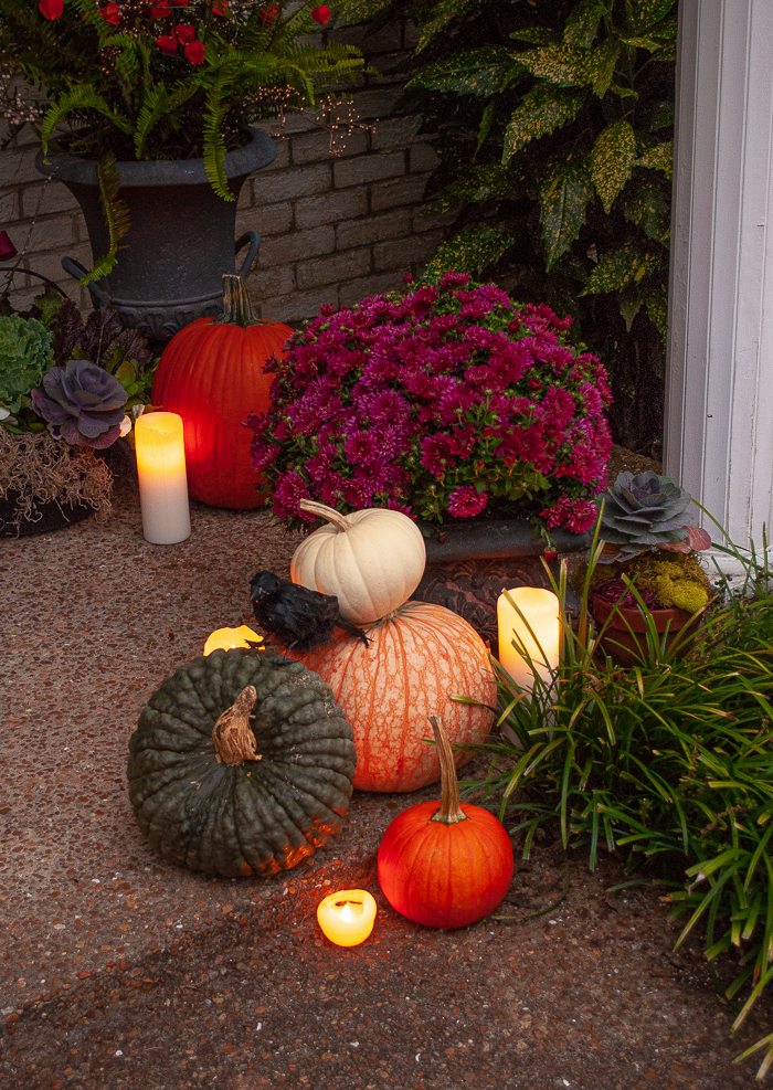 A pile of heirloom pumpkins in green, orange, and white with candles nestled around and a black crow perched on top
