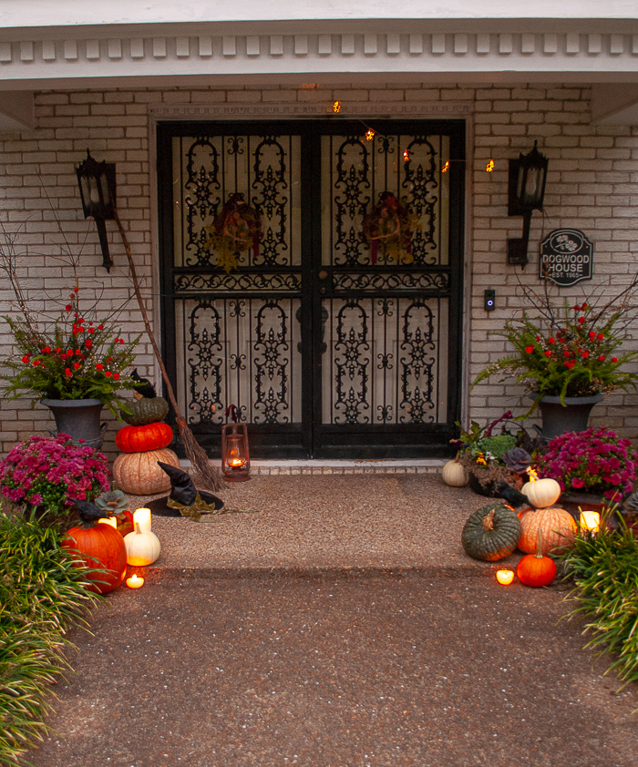 my witchy front door inspired by practical magic with heirloom pumpkins, glowing candlelight, enchanted ferns, purple mums, and witches hat and broom.