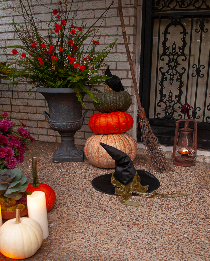 A witches hat tied with green velvet ribbon, twig broom, and old fashioned lantern boost the witch factor at my Halloween front door