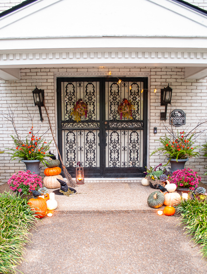 a witchy front door with heirloom pumpkins, purple mums, witches broom and hat, and candles