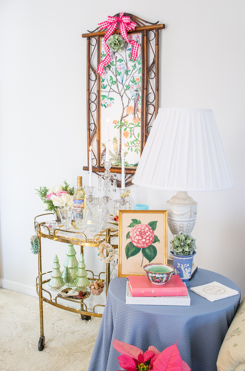 Skirted side table with camellia print, books, and Wedgwood - brass bar cart in background
