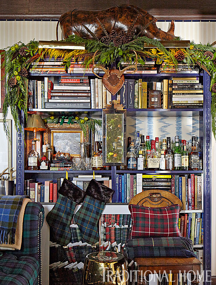 Library shelves decked for the holidays in plaid - Scot Meacham Wood Designs for Traditional Home Magazine