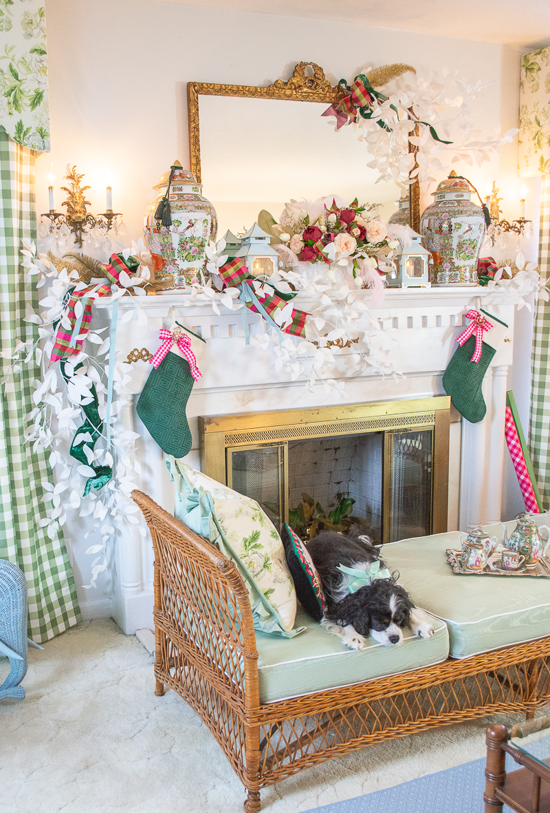 Pink and green color scheme for Christmas decor on white mantel with wicker daybed