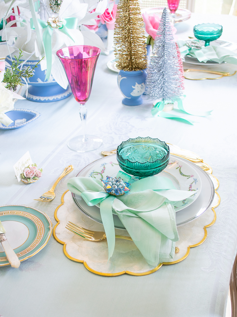 Place setting on Christmas table in Jasperware and Jewels featuring vintage brooch napkin ring from Vintage Meet Modern and green glass coupe