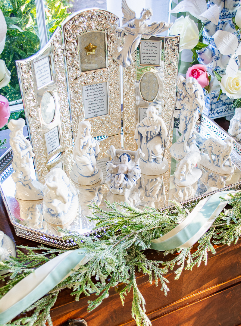 Blue and white Nativity set on silver tray with cedar garland surrounding and silver framed Bible verses in background - top view of Baby Jesus