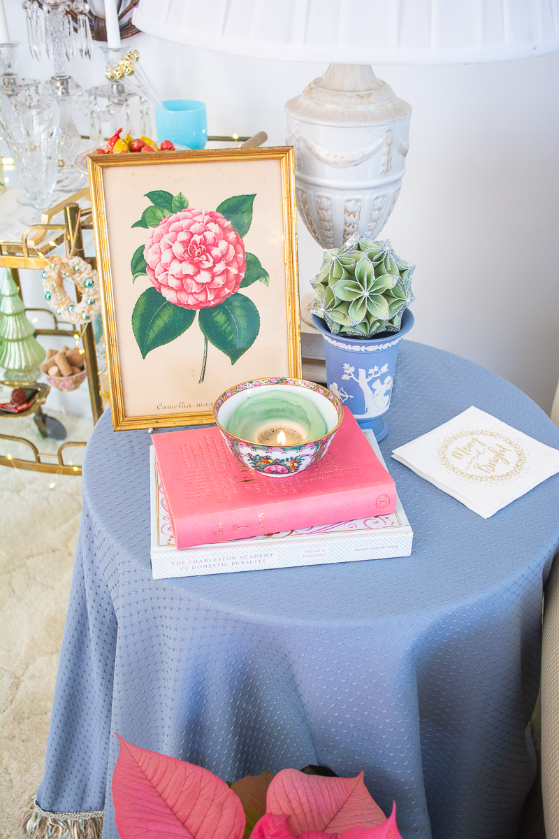 Blue skirted side table with books and candle, Wedgwood vase, and pink camellia print