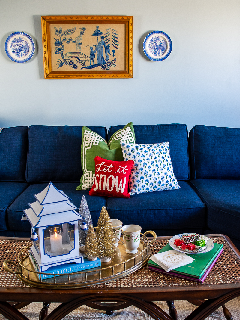 Navy blue sectional sofa with needlepoint pillow and Chinoiserie art on wall above