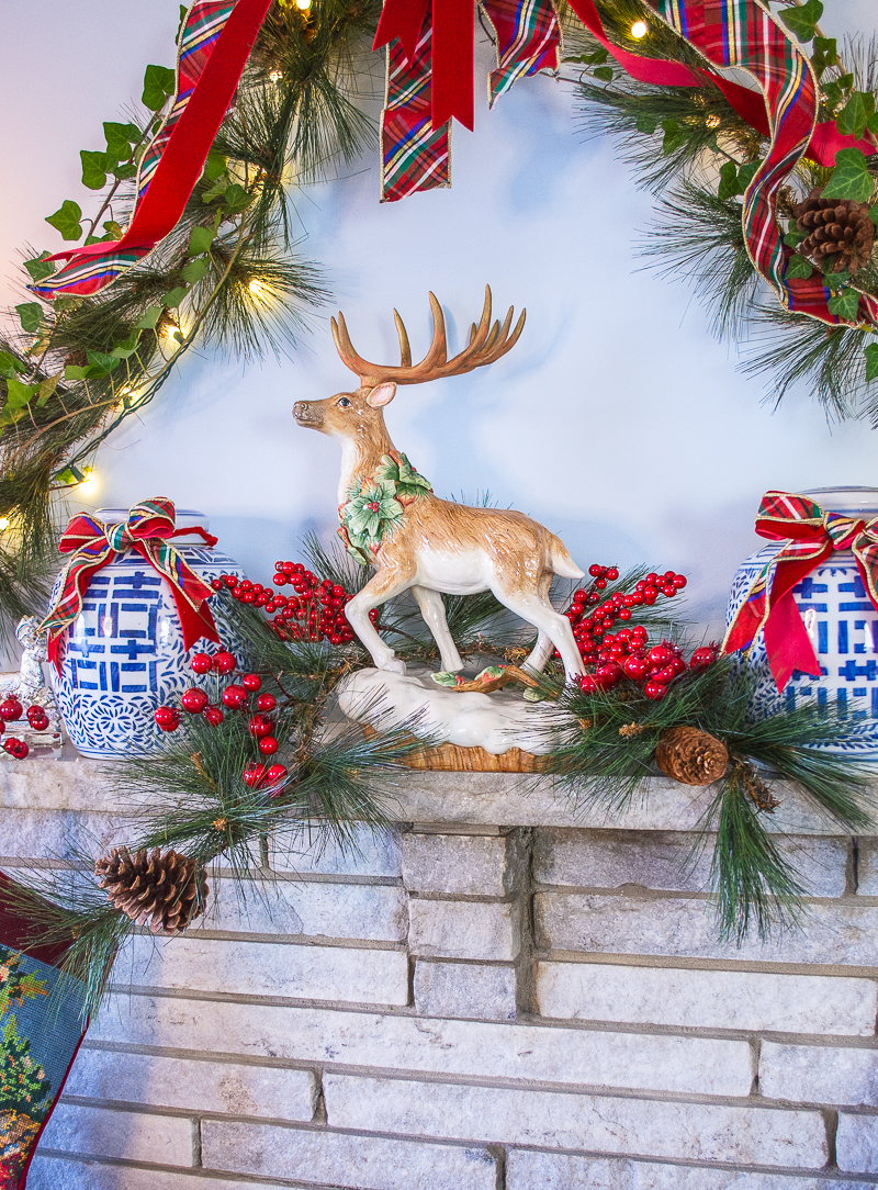 Fitz and Floyd reindeer takes center stage on my holiday mantel decorated with pine and ivy garland, plaid bow, and blue and white ginger jars.
