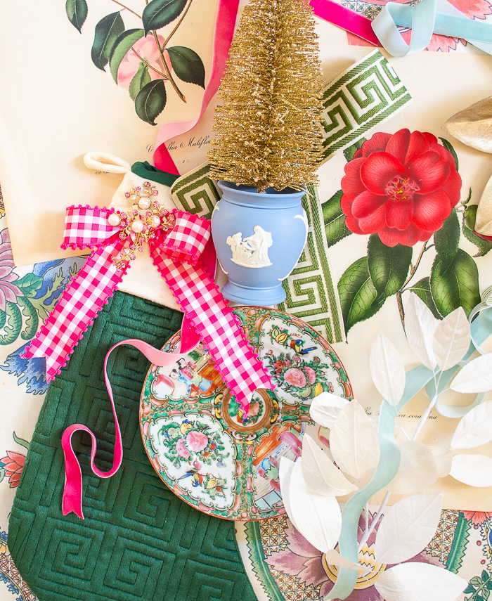 Georgian Chinoiserie Garden Christmas Decoration inspiration shown in flatlay, featuring camellia prints, Wedgwood, pink gingham, Rose Medallion, greek key trim, feathers, and velvet ribbon.