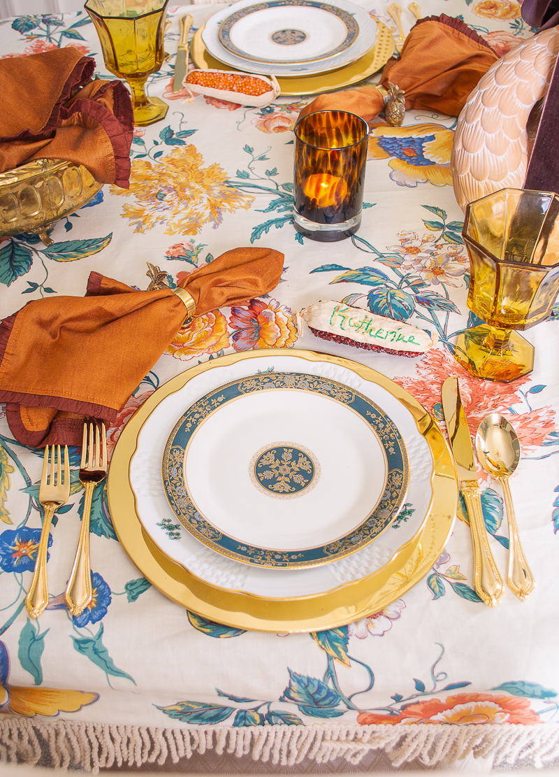 An intimate and chic Thanksgiving celebration with festive tablescape laid with swan and floral centerpiece, chintz tablecloth, brass chargers, Royal Doulton china, and tortoise shell votives