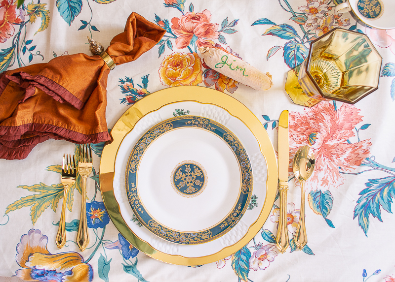 An intimate and chic Thanksgiving table set with chintz tablecloth, Royal Doulton Carlyle china, brown velvet, swan centerpiece, tortoise shell glass candles, and brass chargers