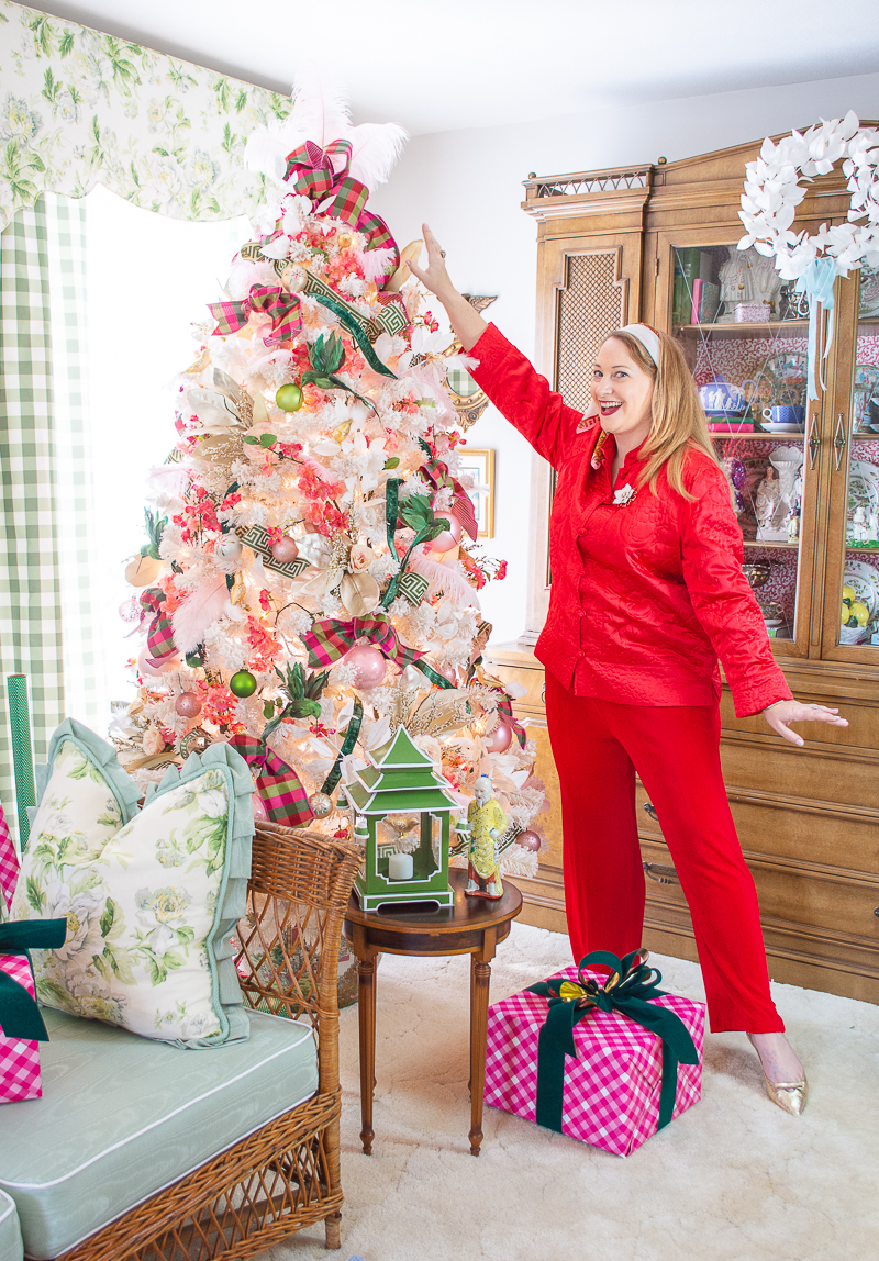 Katherine in oriental red outfit showing off her very Chinoiserie Christmas tree decorated in pink and green
