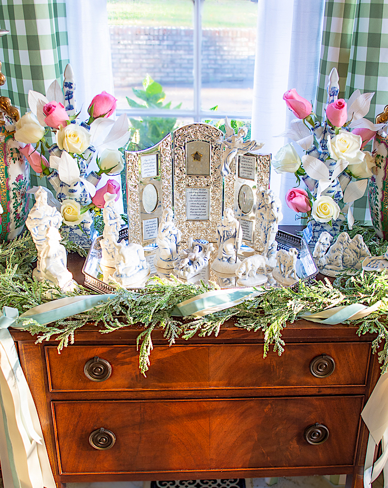 Joyful Nativity scene decoration on sideboard in living room with evergreen garland and roses