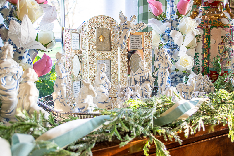 Nativity scene decoration with blue and white nativity figures, silver frame, evergreen garland, and tuliperes with roses