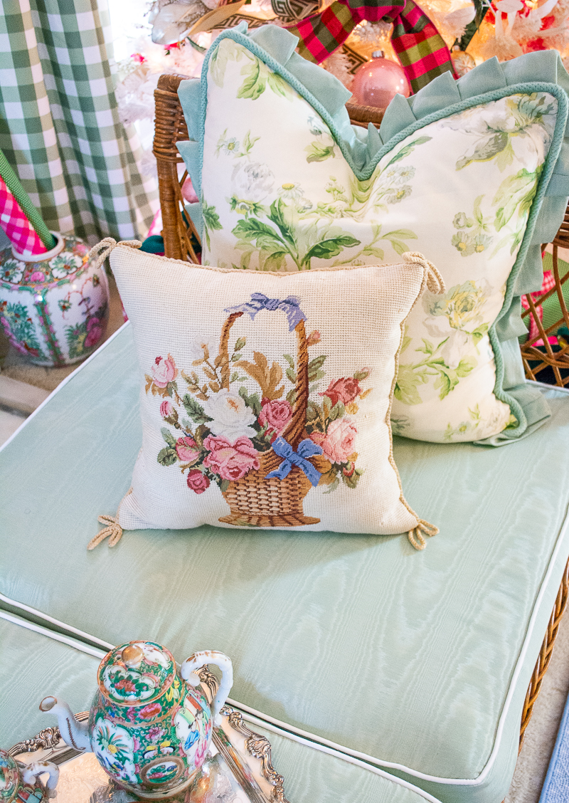 Floral basket needlepoint pillow on wicker day bed with green cushions