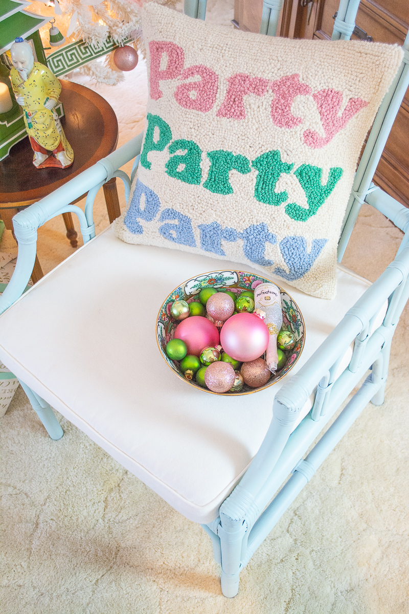 Party party party pillow on rattan chair with bowl of pink and green ornaments