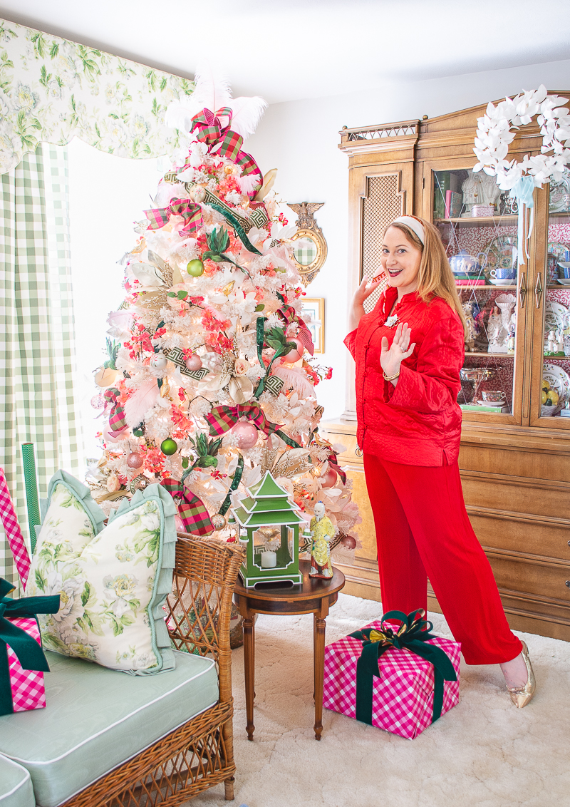 Katherine in red outfit poses with her pink and green Rose Medallion inspired Christmas tree