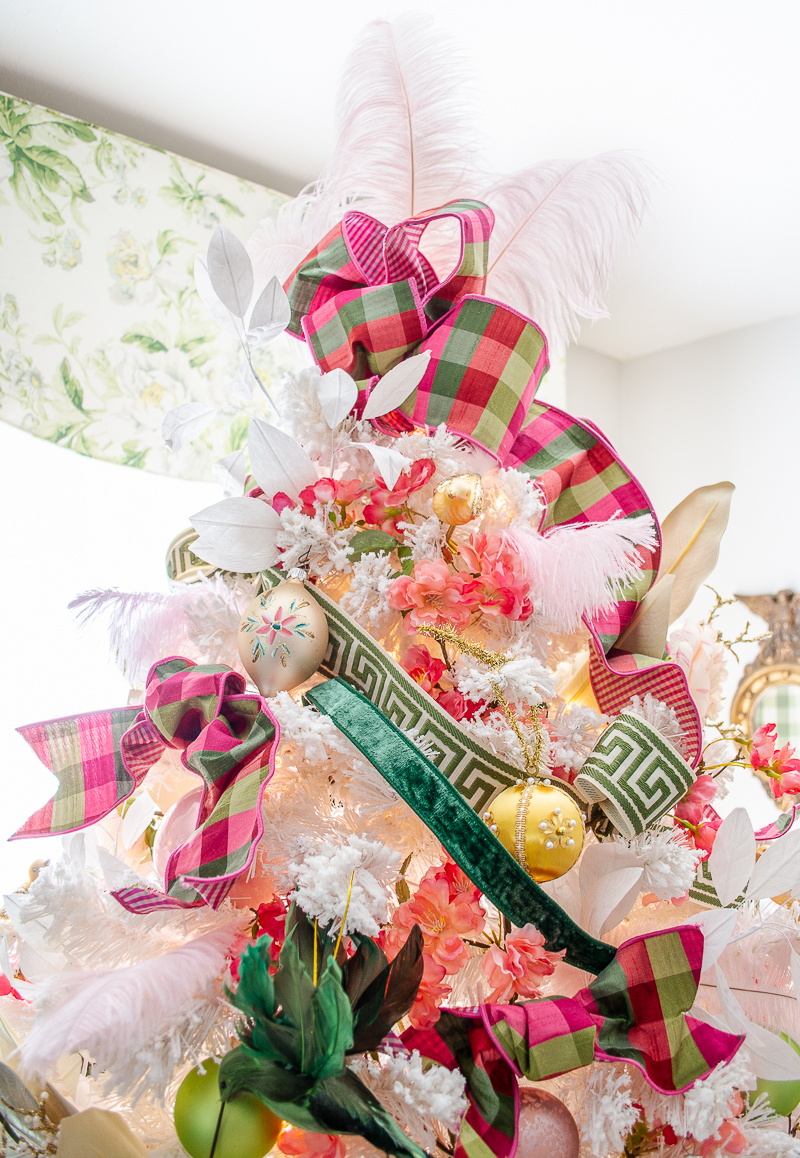 A pink and green plaid bow and pink ostrich feathers top this very Chinoiserie Christmas tree
