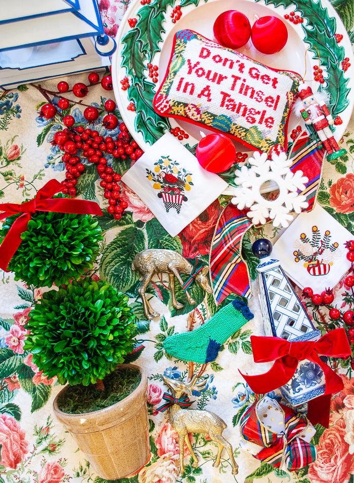 Flatlay showing inspiration for Tartan meet Chinoiserie Christmas Decorations, featuring floral chintz, boxwood topiary, blue and white ceramics, holly, needlepoint, plaid, and red berries