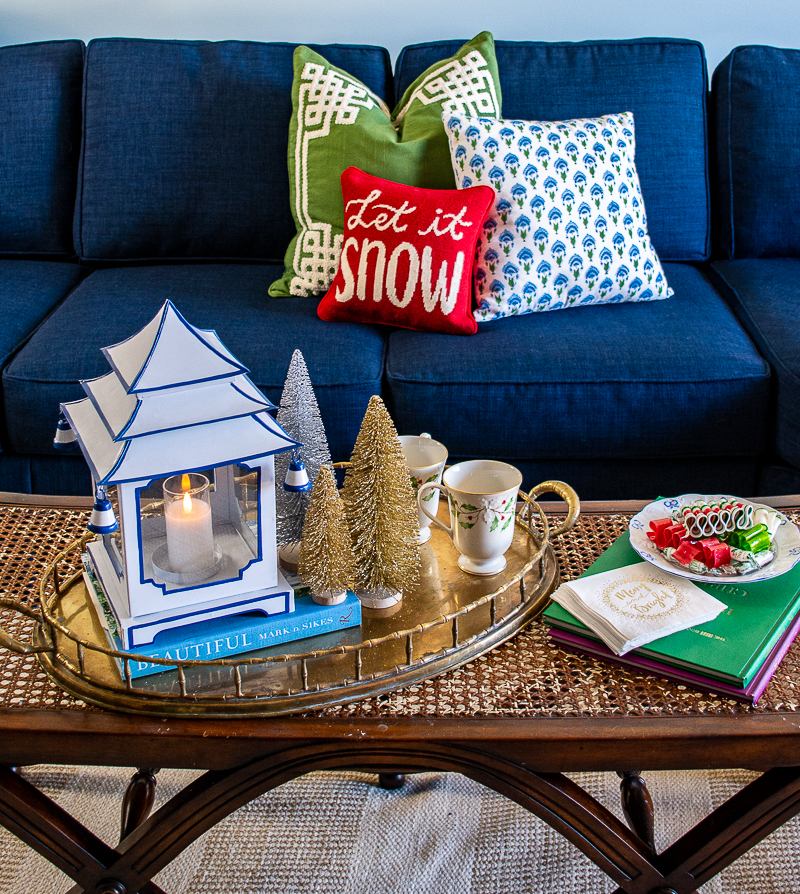 Cane coffee table decorated with Chinoiserie pagoda lantern, vintage brass tray, bottle brush trees, books, and candy