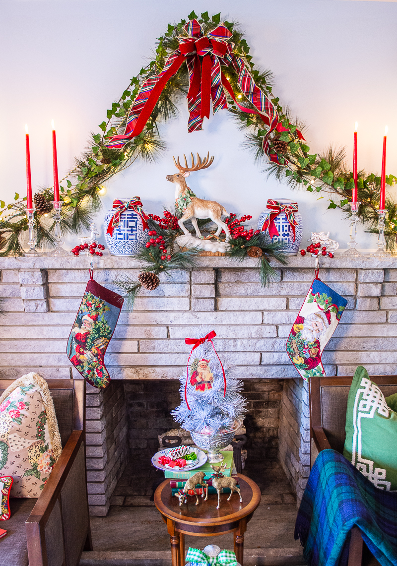 Stone mantel decorated in tartan Chinoiserie traditional Christmas look with pine and ivy garland, plaid bow, reindeer sculpture, and blue and white ginger jars