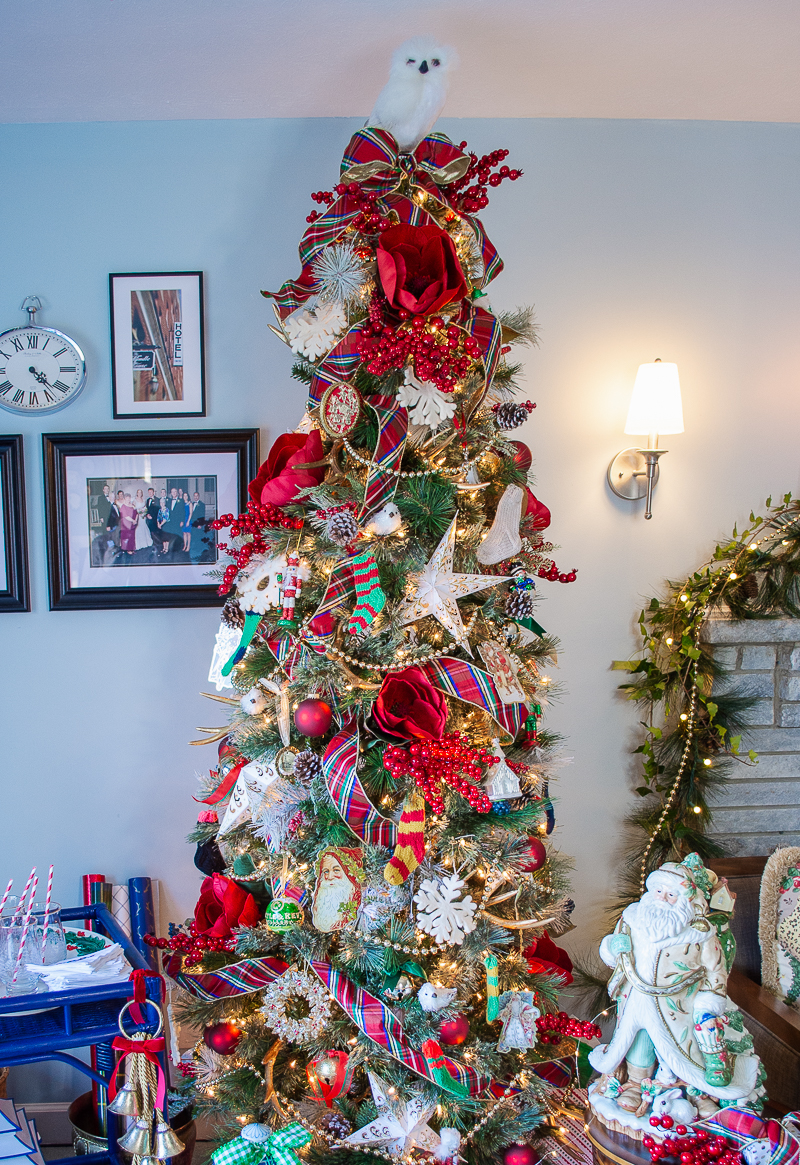 Close up of my tartan meet Chinoiserie traditional Christmas look tree with plaid ribbon, red velvet magnolia blooms, paper stars, mini knit stockings, red berries, and family ornaments.