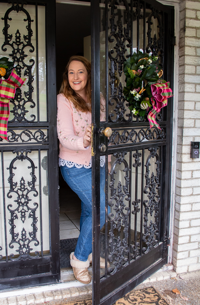Katherine in pink sweater at front door welcoming you to her very Chinoiserie Christmas home tour