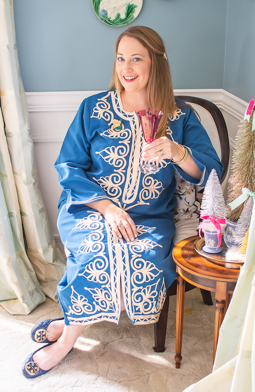 Katherine, the blogger behind Pender & Peony, in blue caftan sitting on chair with pink champagne glass.