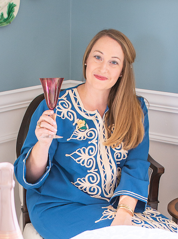 Katherine, the blogger behind Pender & Peony, in blue caftan toasting with pink champagne
