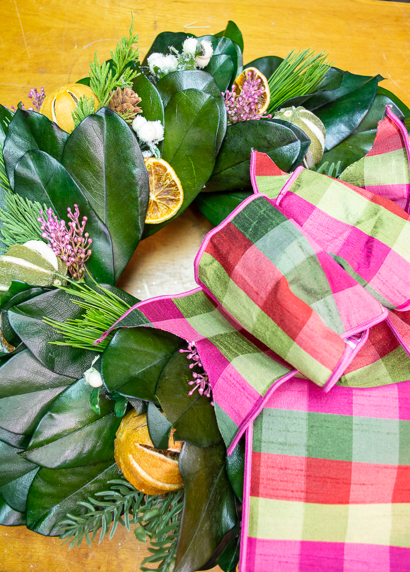 DIY Williamsburg inspired magnolia & citrus Christmas wreath with green and pink plaid bow