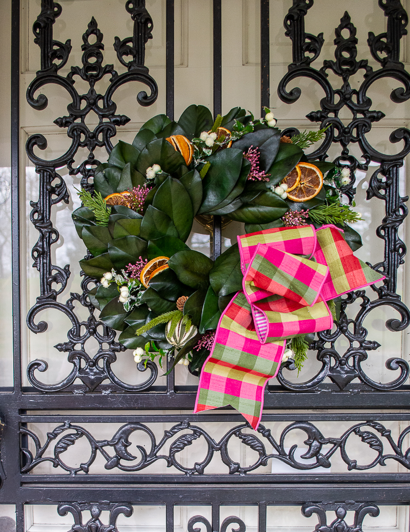 Williamsburg inspired magnolia & citrus wreath with pink and green gingham bow hung on wrought iron front door