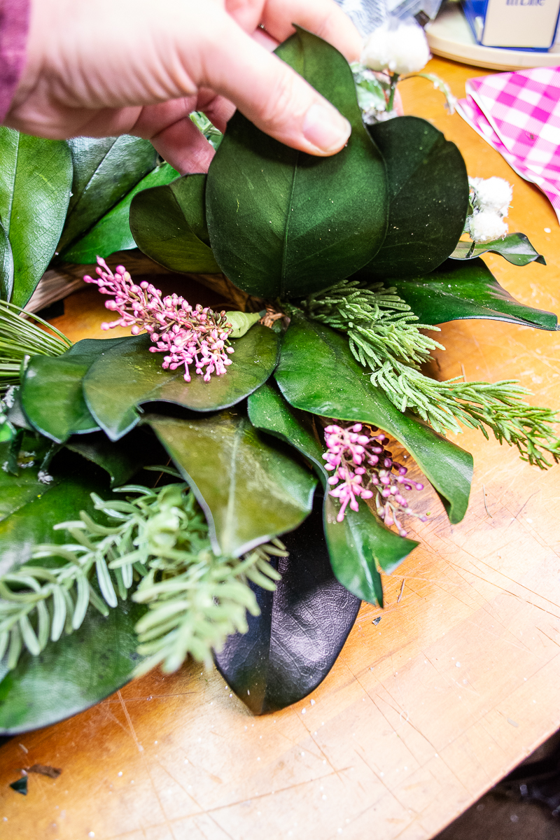 Heather picks added into magnolia and citrus Christmas wreath