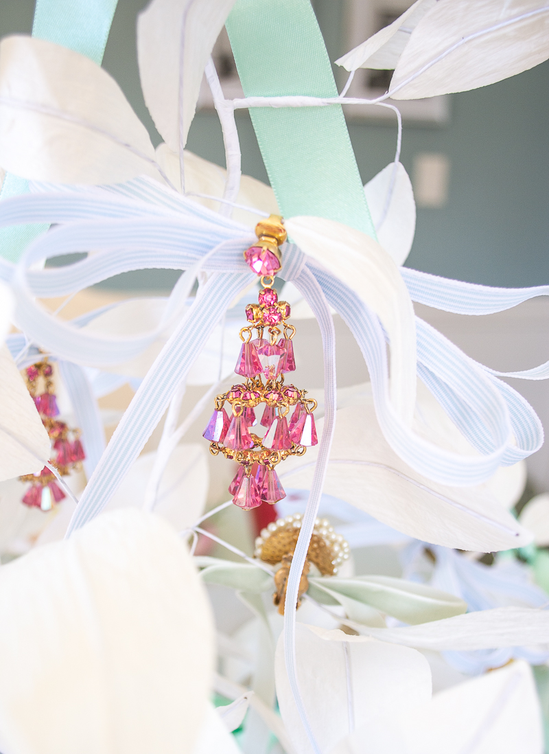 Pink chandelier style earring on A white paper tree nestled in Wedgwood Jasperware compote bedecked with vintage jewelry as ornaments